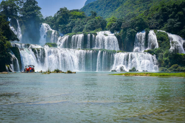 Tourist boats in front of Ban Gioc Waterfall one of Vietnam's best-known waterfalls stock photo