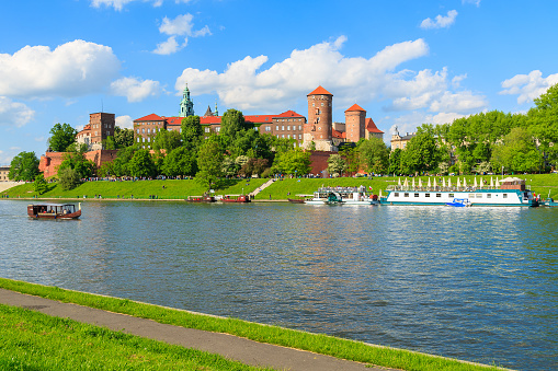 Tourist boats on Vistula river with Wawel Royal Castle in the background on sunny beautiful day, Poland