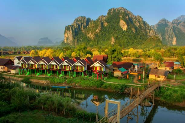 touristischen bungalows entlang nam song river in vang vieng - vang vieng stock-fotos und bilder