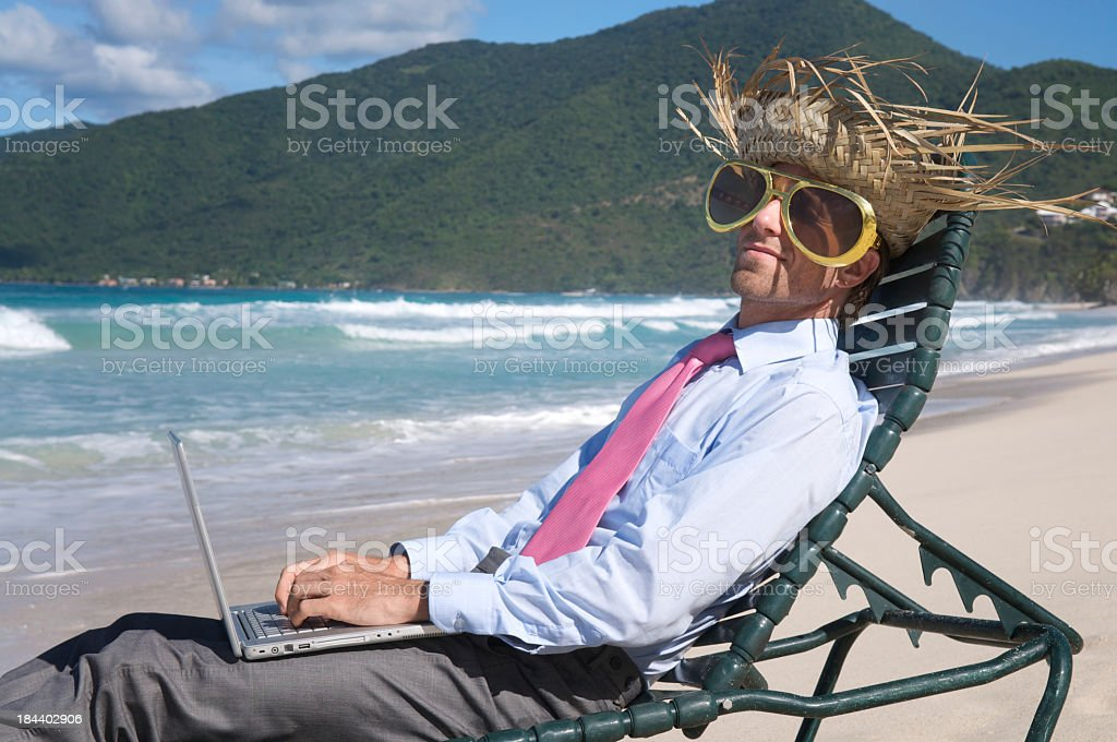 Tourist Businessman Relaxing in Beach Chair with Laptop Computer stock photo