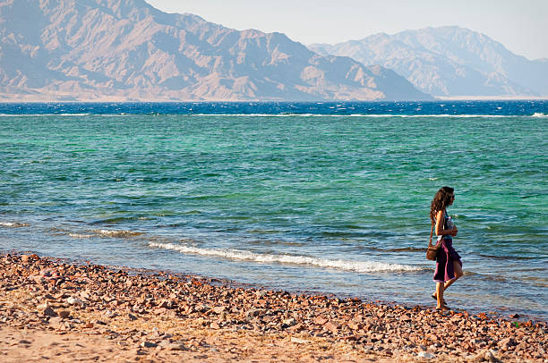 Woman by the Gulf of Aqaba in Dahab, Egypt stock photo