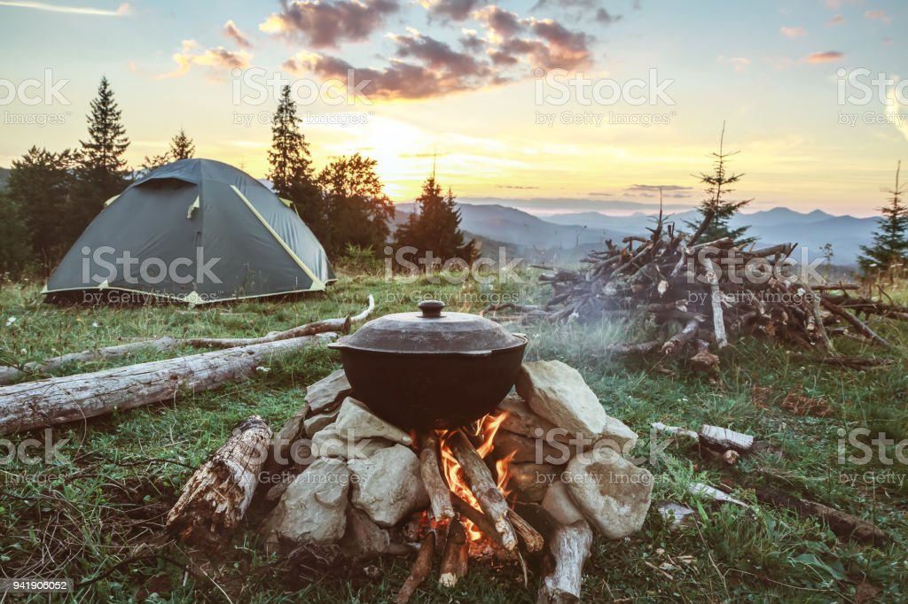 Tourist camp with fire, tent and firewood stock photo