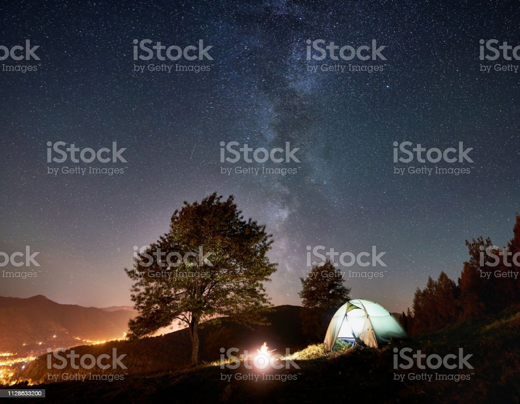 Tourist camping near forest at summer night. Glowing tent and...