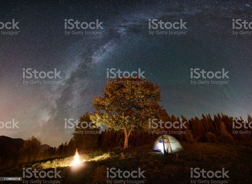 Tourist camping near forest at summer night. Glowing tent and bonfire...