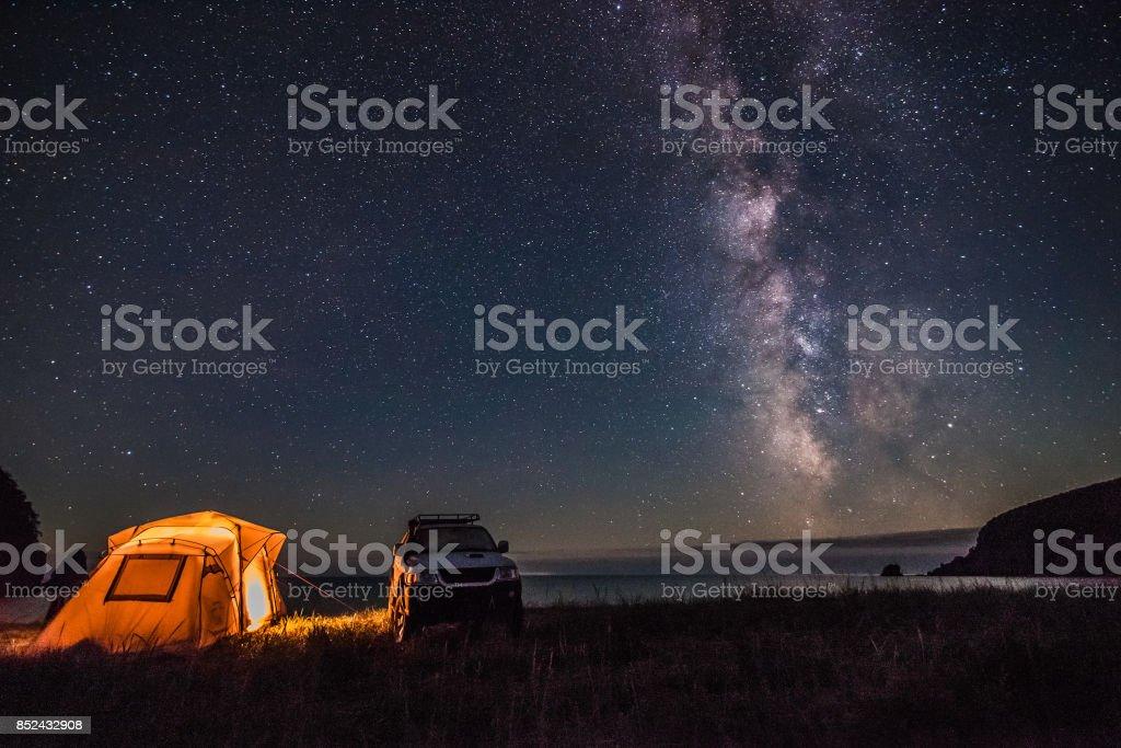 Tourist camping at sea coast at night with milky way stock photo