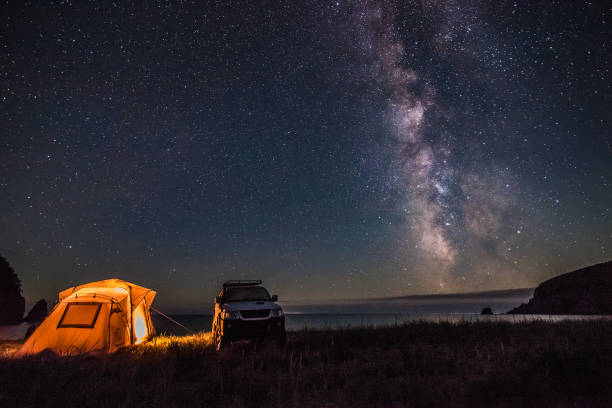 Tourist camping at sea coast at night with milky way stock photo