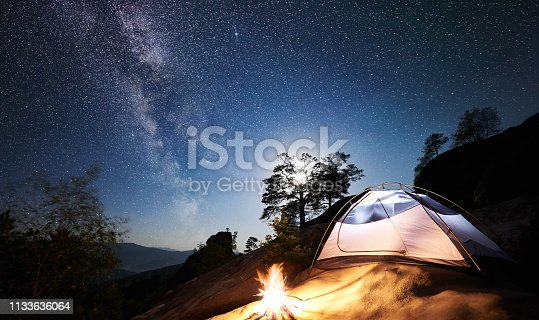 Camping at summer night on rocky mountain. White tourist tent and bonfire under magical night sky full of stars and Milky way. On the background beautiful starry sky, full moon, big boulders and trees