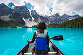 Tourist canoeing on Moraine Lake in Banff National Park, Canadian Rockies, Alberta, Canada.