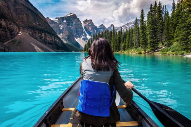 tourist canoeing on moraine lake, banff national park, alberta, canada - moraine стоковые фото и изображения