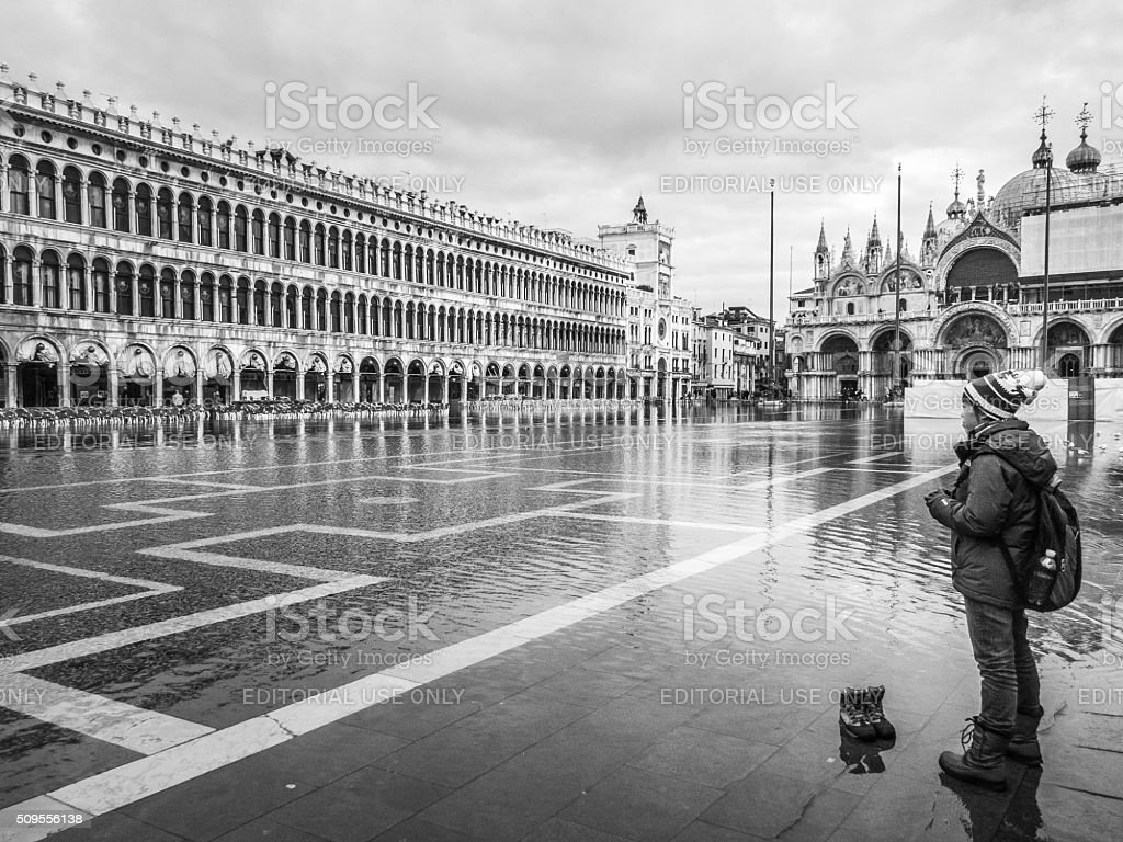 Tourist contemplates crossing a flooded St Mark's Square stock photo