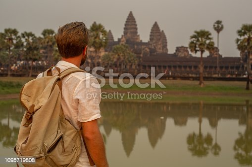 Young man traveling in Cambodia visiting the temples of Angkor wat complex. People travel discovery Asia concept. Shot at sunset, one man only, adventure and exploration in Siem Reap, Southeast Asia.