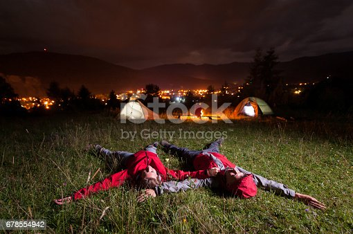 678554980 istock photo Tourist couple admiring the night sky and lying on the grass 678554942