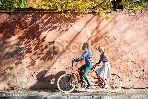 Young attractive happy tourist couple in casual clothing, bearded man and blond woman in glasses cycling together on double tandem bike on background of high red old crackled plastered wall.