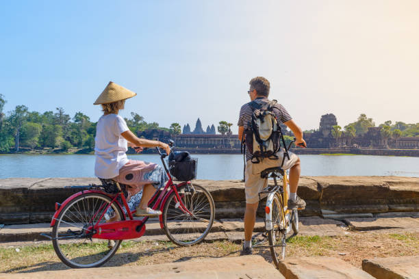 Tourist couple cycling in Angkor temple, Cambodia. Angkor Wat main facade reflected on water pond. Eco friendly tourism traveling. stock photo