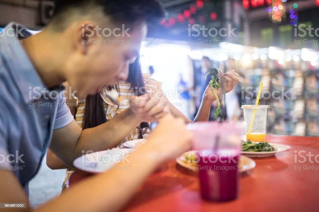 Tourist couple eating street food royalty-free stock photo