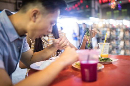 Tourist Couple Eating Street Food Stock Photo & More Pictures of 20-24 Years