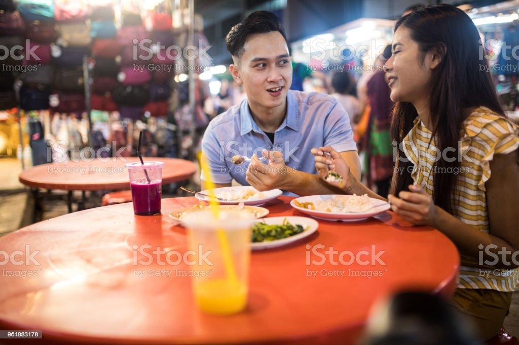 Tourist couple eating street food royalty-free stock photo