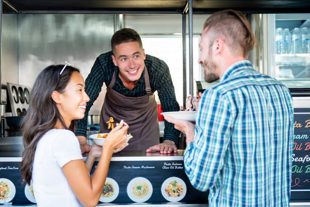 Tourist couple enjoy eating pasta from food truck Tourist couple enjoy eating pasta from food truck at outdoor market food truck stock pictures, royalty-free photos & images
