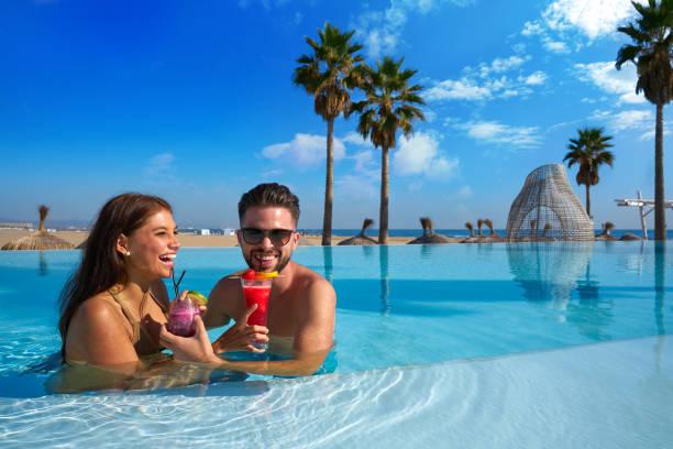 Tourist couple having bath in infinity pool stock photo
