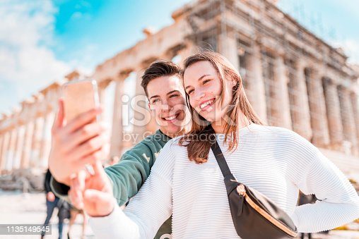 Tourist couple taking a selfie  in Acropolis - Athens.