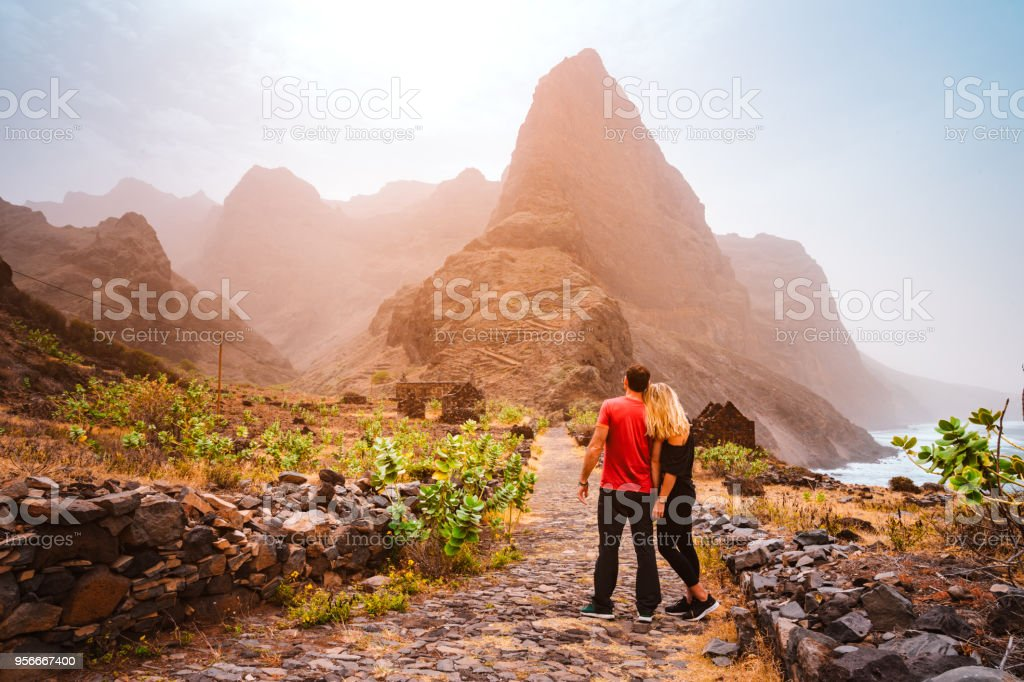 Tourist couple in Aranhas valley hiking from Cruzina to Ponta do Sol. Huge mountains of coastline and old local stone house in the background. Santo Antao Island, Cape Verde stock photo