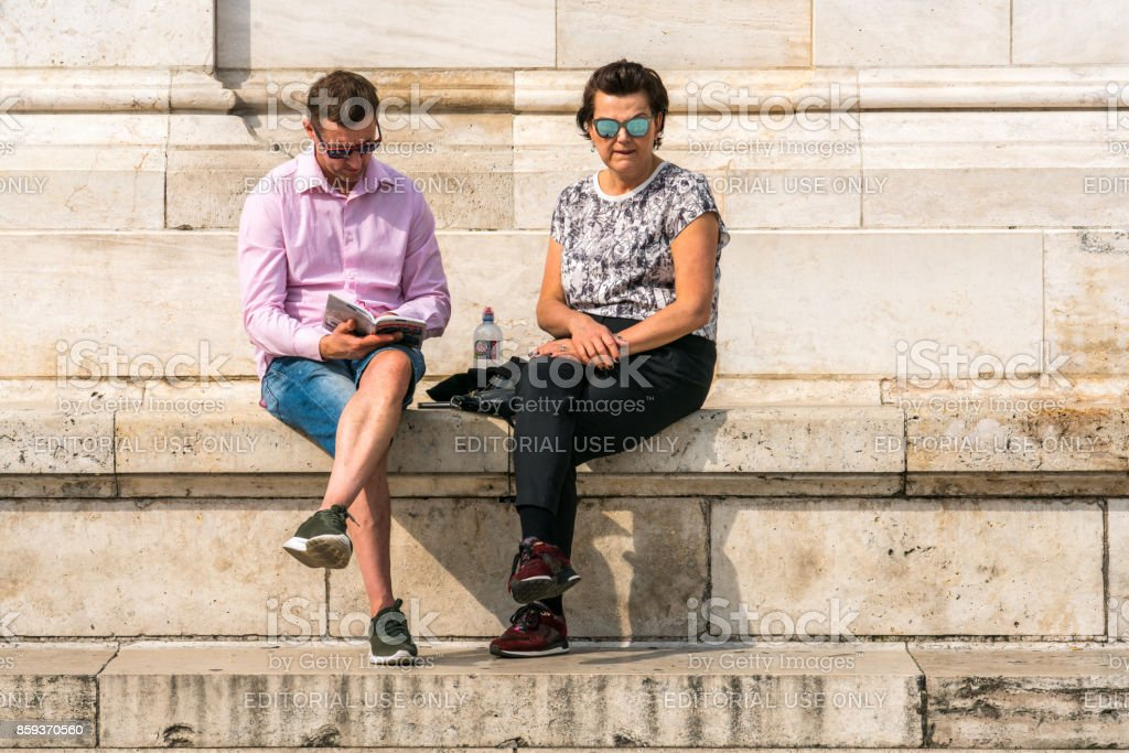 Tourist couple in Budapest wearing sunglasses resting at marble stairs. royalty-free stock photo