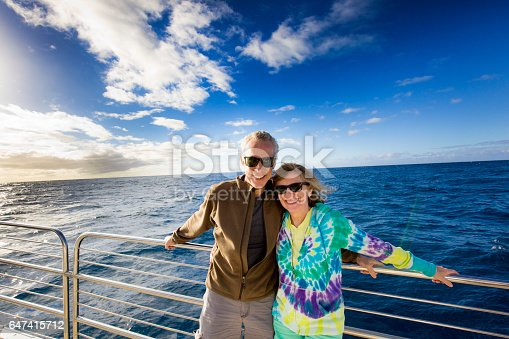 Mature adult tourist couple enjoying cruise ship boat tour. Photographed on location in Hawaii in horizontal format with copy space available.