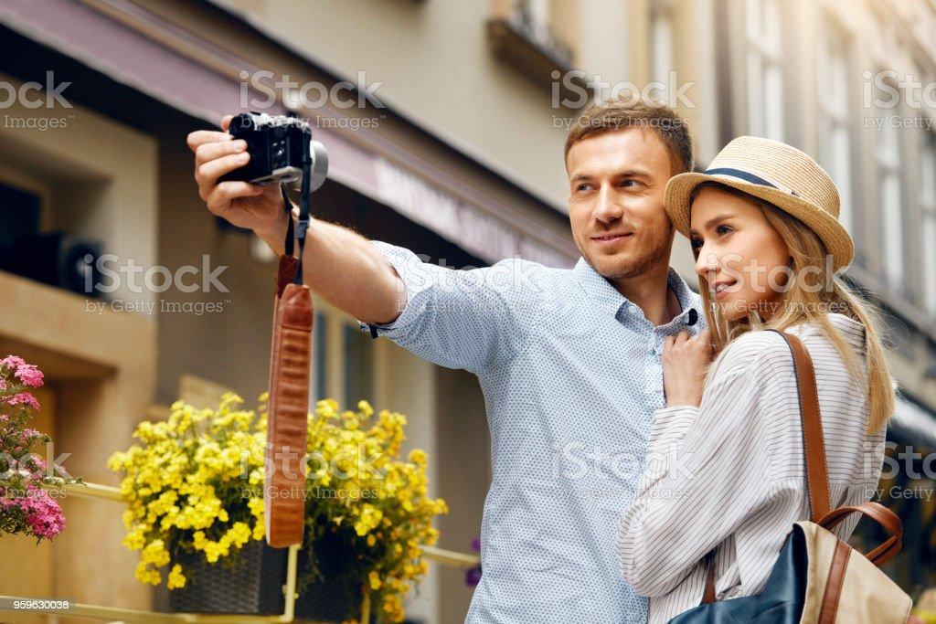 Pareja de turistas en el amor tomar fotos durante el viaje. - Foto de stock de A la moda libre de derechos