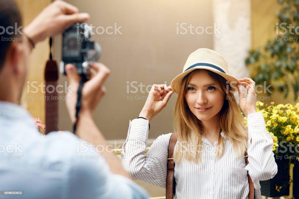 Pareja de turistas. Hombre con la cámara tomando fotos de la mujer en la calle - Foto de stock de Actividad de fin de semana libre de derechos