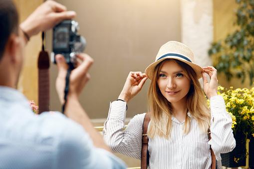 Pareja De Turistas Hombre Con La Cámara Tomando Fotos De La Mujer En La Calle Foto de stock y más banco de imágenes de Actividad de fin de semana