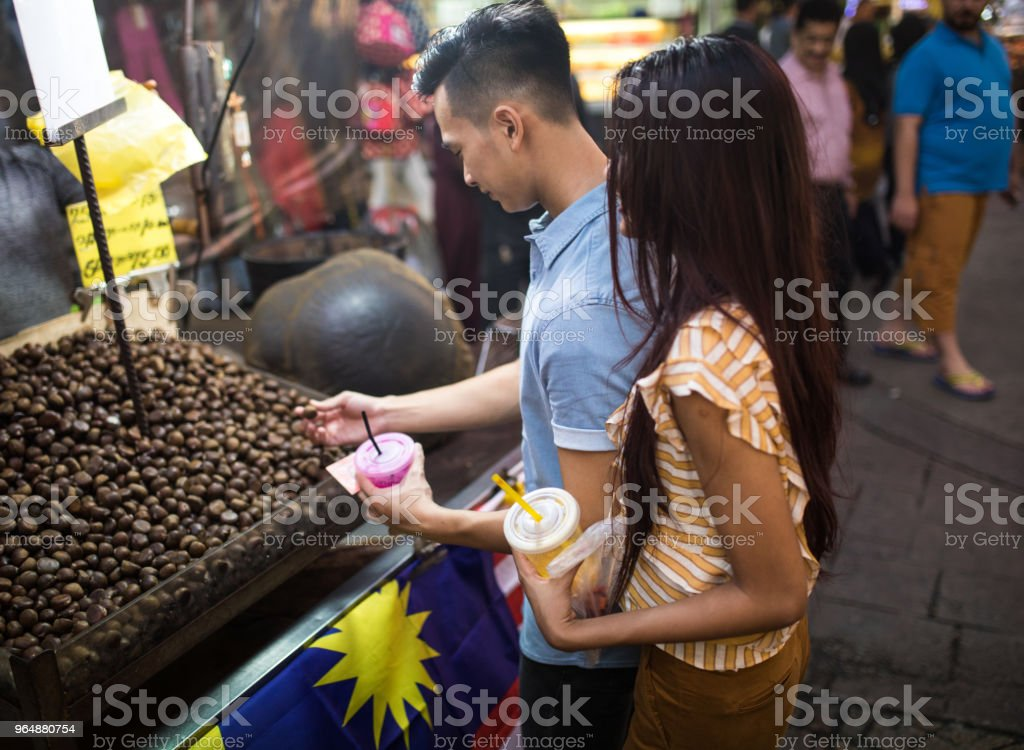 Tourist couple picking chestnuts at the Jalan Petaling market royalty-free stock photo