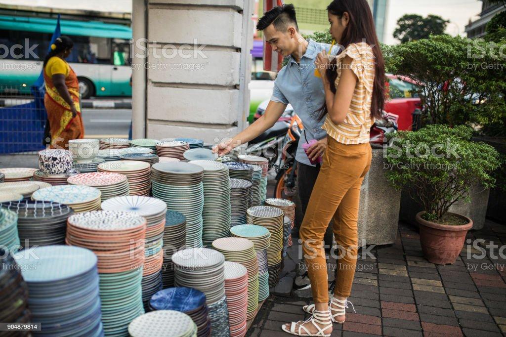 Tourist couple picking plates at the Jalan Petaling market royalty-free stock photo