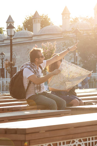 tourist couple reading map and traveling in istanbul - jugendweihe 2016 stock-fotos und bilder