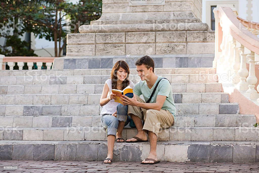 Tourist couple sitting on steps royalty free stockfoto