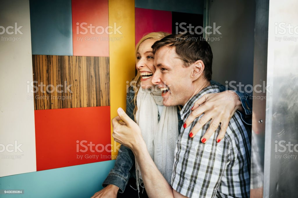 Tourist Couple Smiling While Using Photo Booth Together stock photo