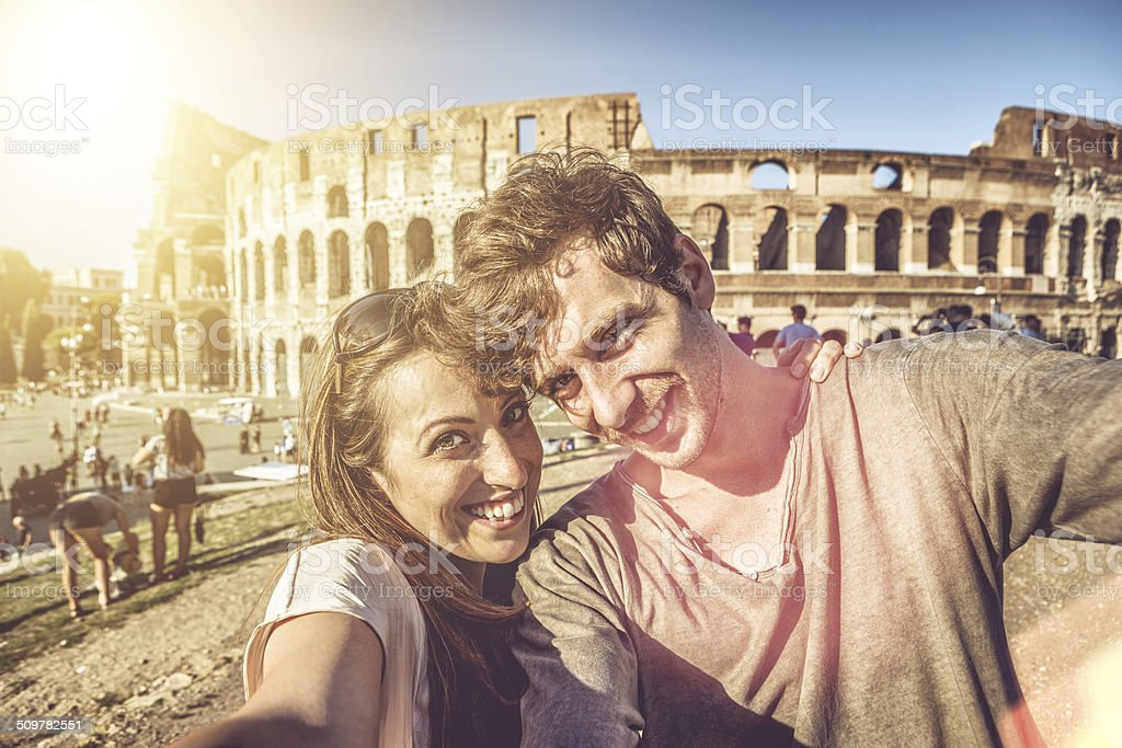 Tourist couple taking a selfie in front of the Coliseum stock photo