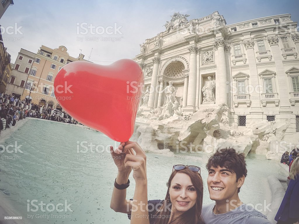 Tourist couple taking a selfie with heart at Trevi fountain stock photo