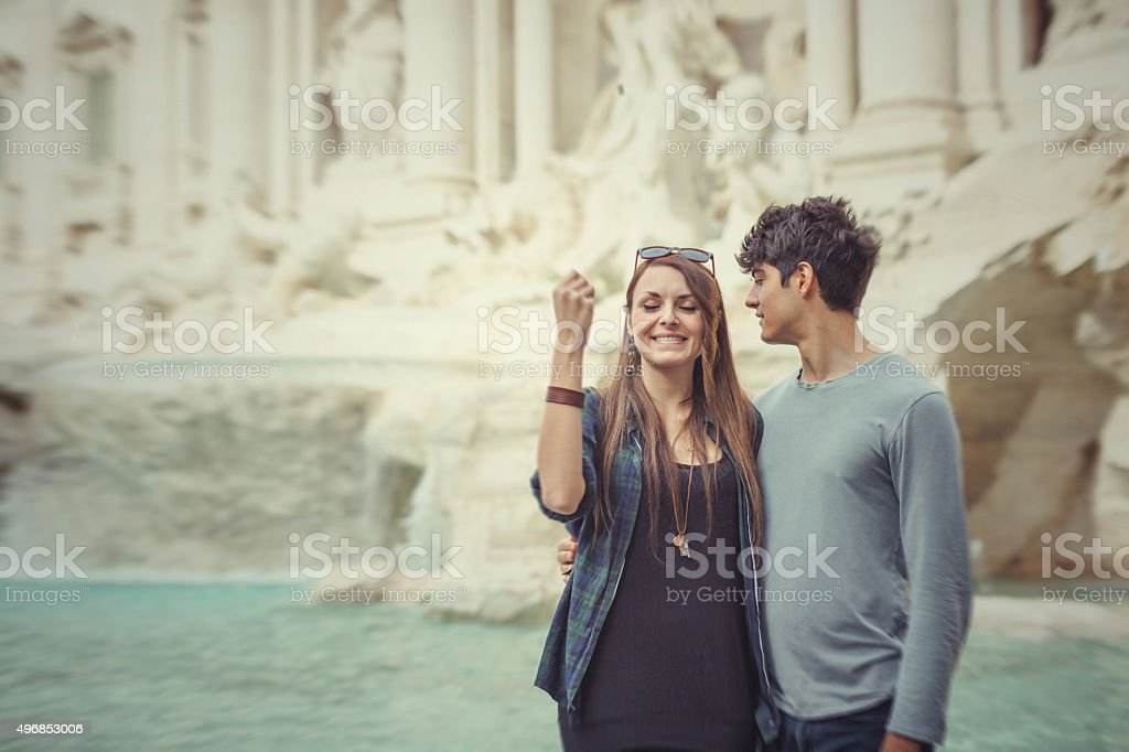 Tourist couple throwing a coin in the Trevi fountain stock photo