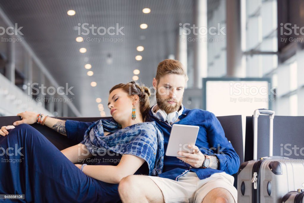 Tourist couple waiting for their delayed flight stock photo