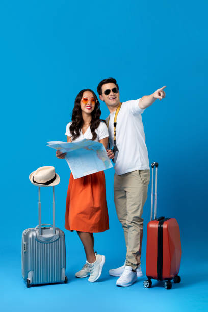 Tourist couple with baggage in blue studio background stock photo