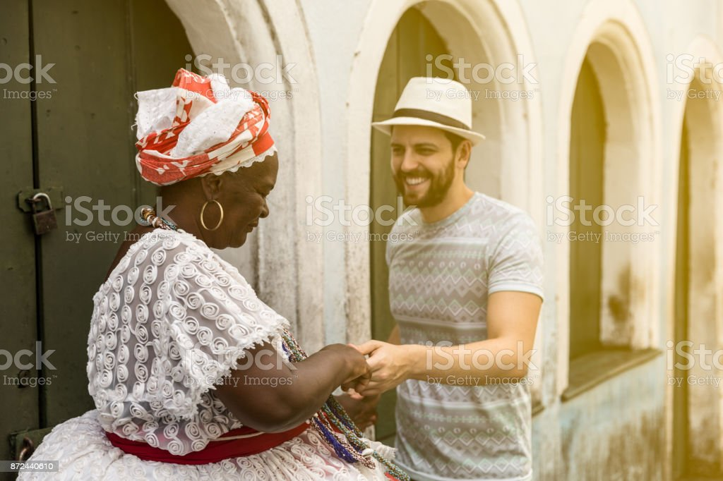 Tourist dancing with 'Baiana' woman in Pelourinho, Salvador, Bahia, Brazil stock photo