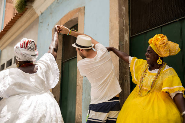 "tourist dancing with local brazilian woman ""baiana"" in pelourinho, salvador, bahia, brazil - south america travel stock photos and pictures"