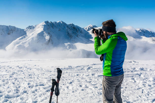 Tourist does photo camera, winter mountain scenery. stok fotoğrafı