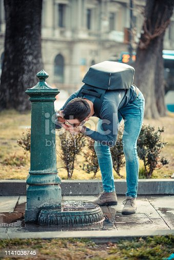 Tourist Drinking Water From Public Fountain