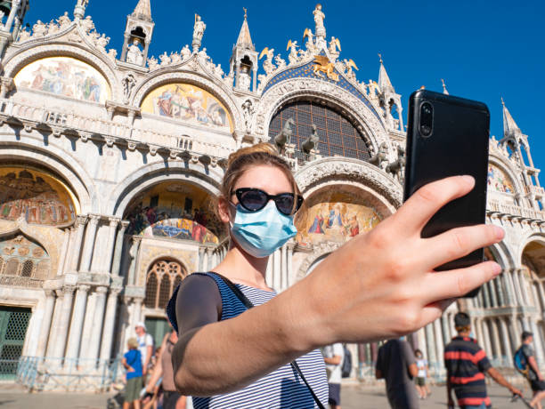 A tourist during the coronavirus pandemic, covid-19. A young woman wears a surgical mask in Piazza San Marco, in the background Cathedral Basilica of Saint Mark. A famous destination in Italy. stock photo