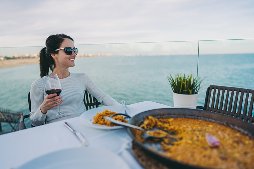 Woman in restaurant eating traditional spanish paella with glass of red wine
