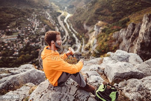 Young man in the mountain sitting on the rocks and eating breakfast with cup of hot tea