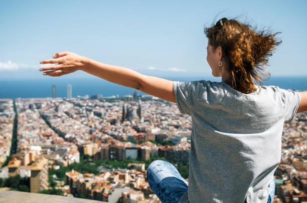 Tourist enjoy of the view from above of Barcelona city and the Mediterranean sea, Catalonia, Spain. stock photo