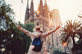 Rear view of young woman in front of Sagrada Familia with arms outstretched enjoying the beautiful city