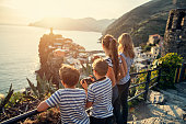 Family sightseeing Cinque Terre - a UNESCO World Heritage Site. The family is looking at the view of Vernazza on sunset.\nNikon D850